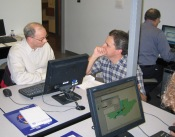 Lee and Peter compare notes while maps emerge on monitors.
